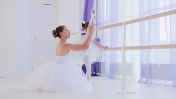 Ballet teacher is teaching little girl to stretch legs near the barre stand.