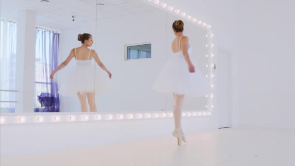 Ballerina in white tutu is practicing dance elements in front of the mirror.