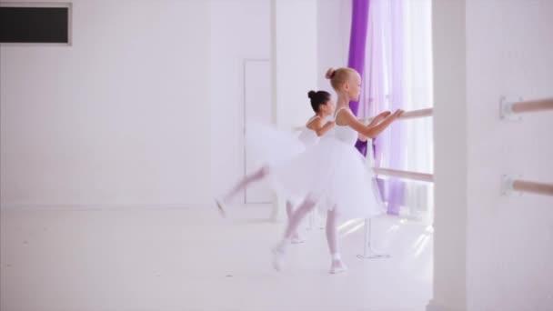 U Barre v baletu se zahřívá dva dětské baletky.