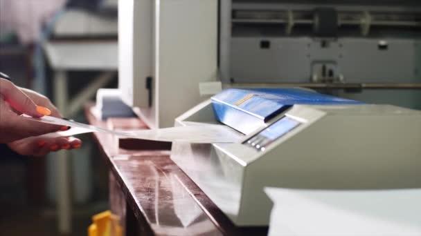 Žena v typografii laminuje papír v laminátoru.