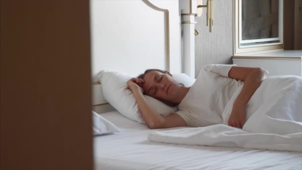 Young caucasian woman is sleeping at home and slowly waking up and stretching.