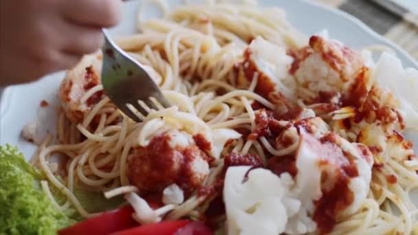 ein kleines Mädchen isst Spaghetti in Großaufnahme