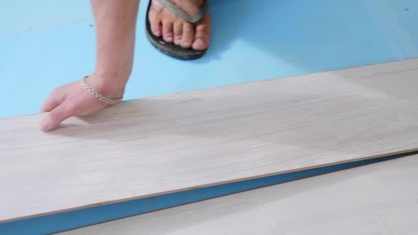 Dělník vkládá laminát do místnosti, proces podlahy.