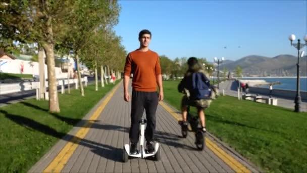 Muž jede segway ve městě na nábřeží, pohled zepředu
