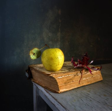 Still life with a book, an apple and a maple leaf. vintage