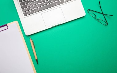 Modern workspace. Computer laptop and notepad on green color office desk, top view, copy space