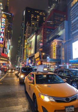 New York City at night. 42nd Street traffic and neon signs.