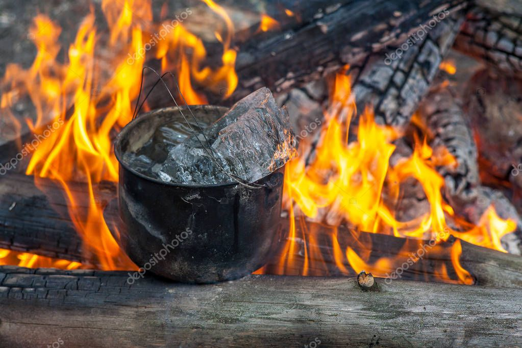 Cooking in the nature. Cauldron with ice on fire in forest. Kitchen in travel.