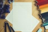 Fotografia Vista superiore di colorare matite colorate accanto il libro disegno schizzo su fondo di legno