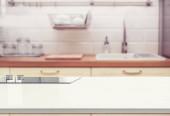 Dřevěný stůl top na rozmazané kuchyňské místnosti pozadí. mohou být použity pro zobrazení nebo montáž vašich produktů