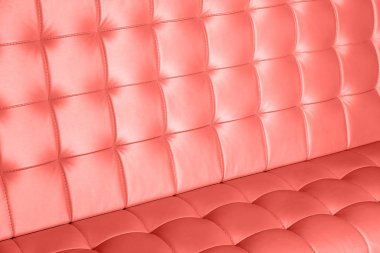 Closeup surface of luxury leather sofa of living coral color as texture or background
