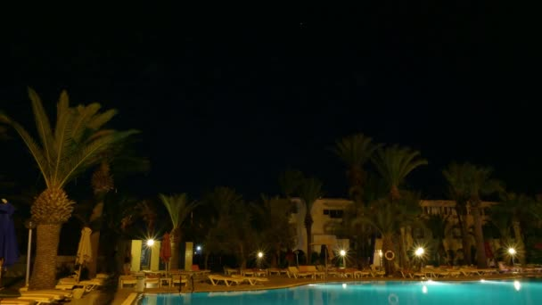 Night swimming pool with lighting and palm trees in luxury time lapse