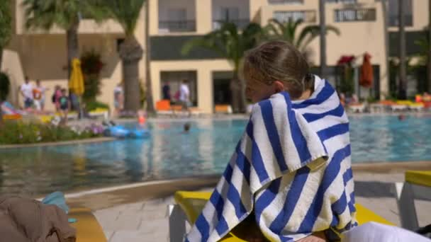 Young wet girl wrapped in towel sits on sunbed near swimming pool