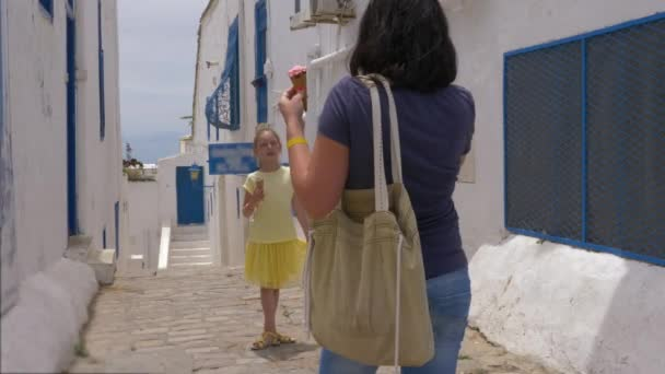 Young mother doing photo to daughter on narrow street background in summer city