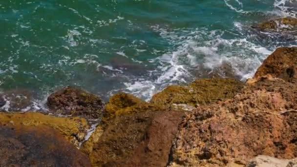 Pohled shora na mořské vlny stříkající o velké kameny na břehu