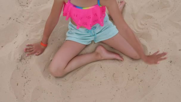 Adorable blonde girl find blue sandal in sand, top view