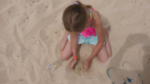 Girl palying with wet sand on beach, top view