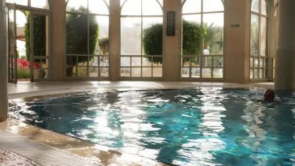 Man swimming in fresh water with flares and resting in indoor pool