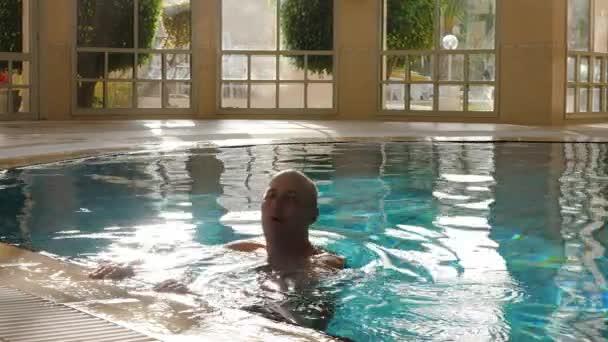 Znak plavání dospělých holohlavý muž s splash v krytém bazénu