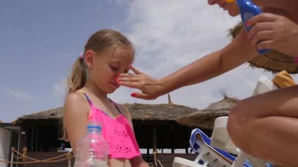 Mladá matka použití opalovací krém na obličej kůži dceři na pláži