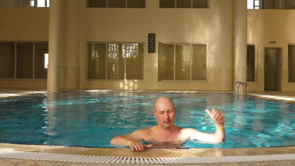 Male swimmer getting out of indoor swimming pool