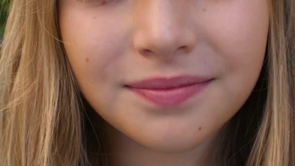 fröhliches Mädchen mit zahmem Lächeln und rosa Lippen, Teilsicht
