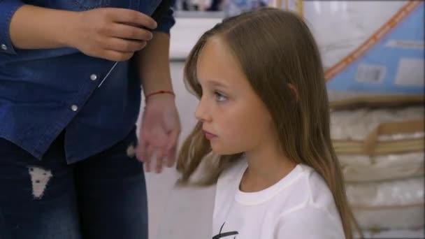 Hairdresser making hairdo for adorable girl in beauty salon