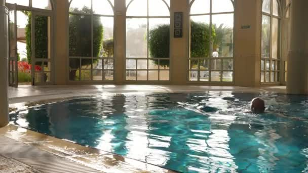 Athlete man swimming in pool and come out from water in resort hotel