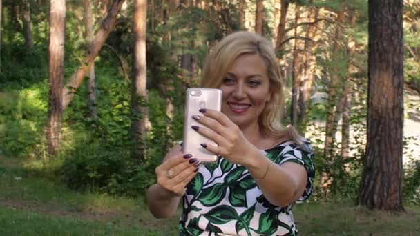 Happy woman using mobile phone for video calling in summer park