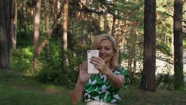 Šťastná žena mává na video chat s smartphone v lese venkovní