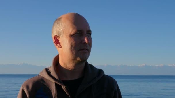 Pohledný muž tvář na horskou krajinu a jezero Issyk-Kul zblízka