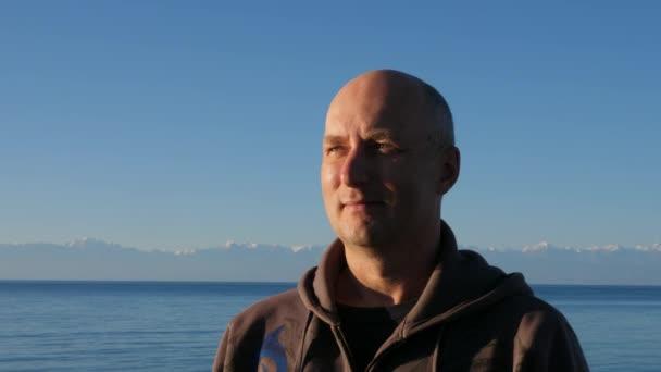 Portrét muže na horské vrcholy a modré jezero Issyk Kul krajina