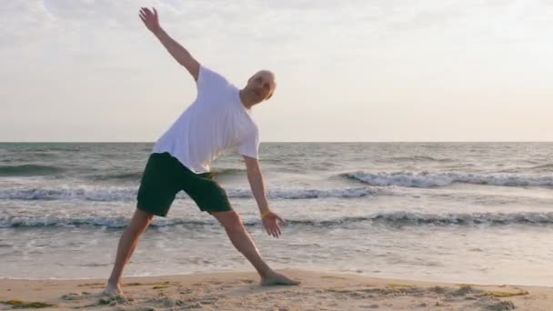 Athletic man practicing yoga in extended triangle asana on sea shore
