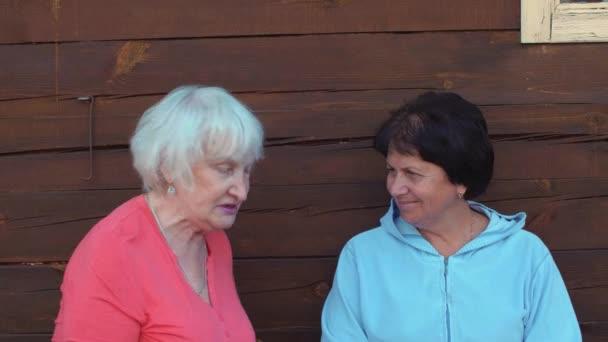 Portrét dvě starší žena pózuje a při pohledu kamery na dřevěné stěně obrazce pozadí