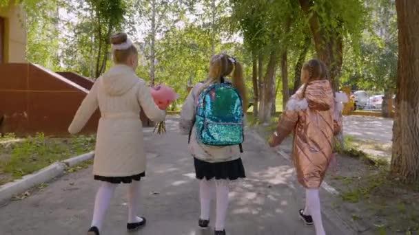 Három lány virág csokrok gyalog az iskolába, hátulnézet