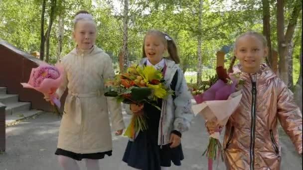Tři dívka s květy kytice do školy. Zpátky do školy koncept