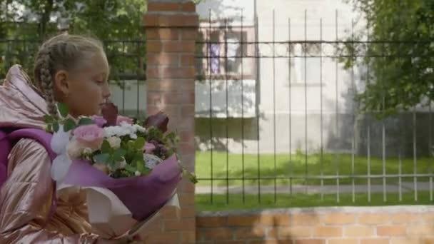 Komoly lány csokor virággal vissza az iskolába. Vissza a concept iskolai