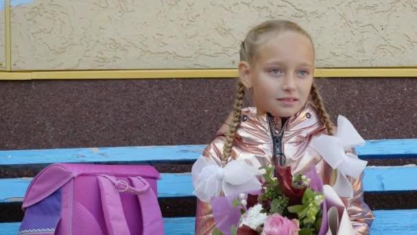 Školy dívka s kyticí květin portrét sedí na lavičce. Zpátky do školy koncept