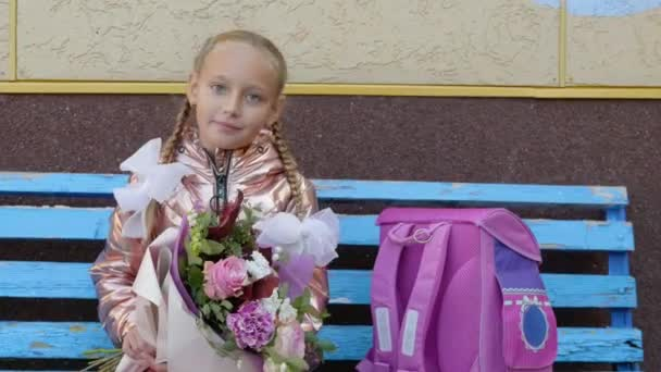Boldog iskolás lány ül a padon csokor virággal. Vissza a concept iskolai