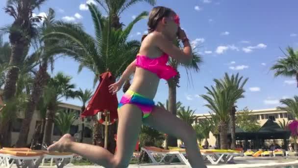 Dívka v brýle skákání a potápění v bazénu na tropický resort