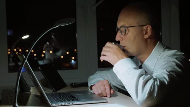 Erwachsener Geschäftsmann trinkt Wasser aus Glas und arbeitet mit Laptop im Nachtbüro