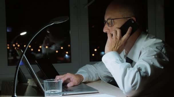 Geschäftsmann plaudert während seiner letzten Arbeit im Büro mit dem Handy