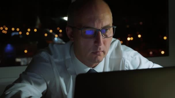 Adult businessman working to laptop computer at last evening in dark office