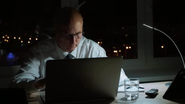 Výkonný obchodník brýlemi a pracují na notebooku na pracovišti v večer