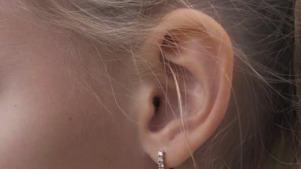 weibliches Ohr mit Ohrring in Großaufnahme. Ohr der Blondine mit dekorativem Piercing
