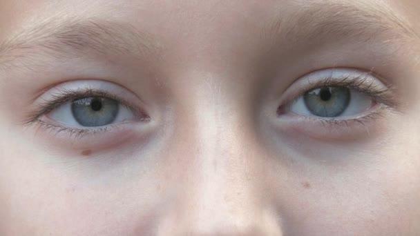 Teenager s šedýma očima při pohledu na neveřejné closeup. Děti tvář s šedýma očima