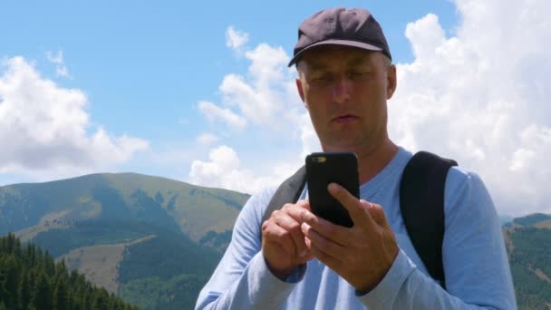 Adult man using mobile phone in mountain landscape, low angle view. Traveling man holding and browsing smartphone while travel in mountain valley