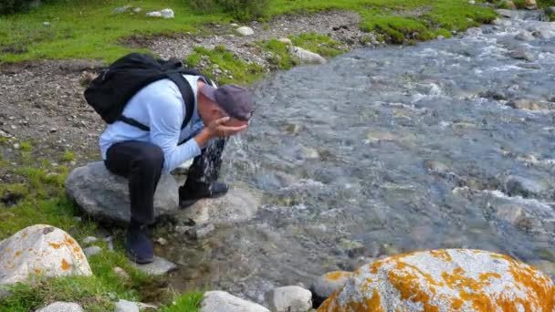 Man washing face by cold water on stony river shore in mountain valley