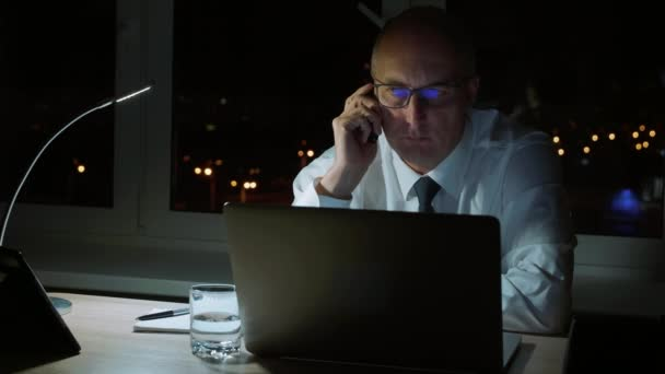 Executive businessman talking to phone sitting at table in dark office at night