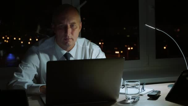 Focused businessman taking eyeglasses and working to laptop in night office